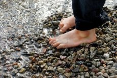 8305324-two-small-feet-on-pebbles-on-the-beach
